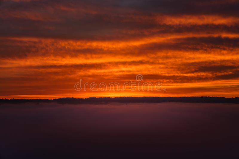 O por do sol vermelho nubla-se com fumo através dos fundos do oceano fotos de stock