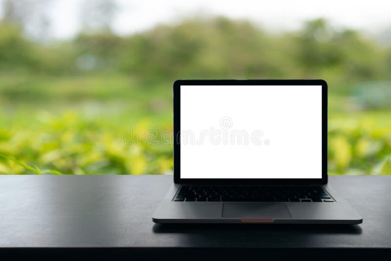 O portátil com a tela vazia na tabela, espaço de trabalho conceptual, laptop com a tela branca vazia na tabela, esverdeia o backg fotos de stock