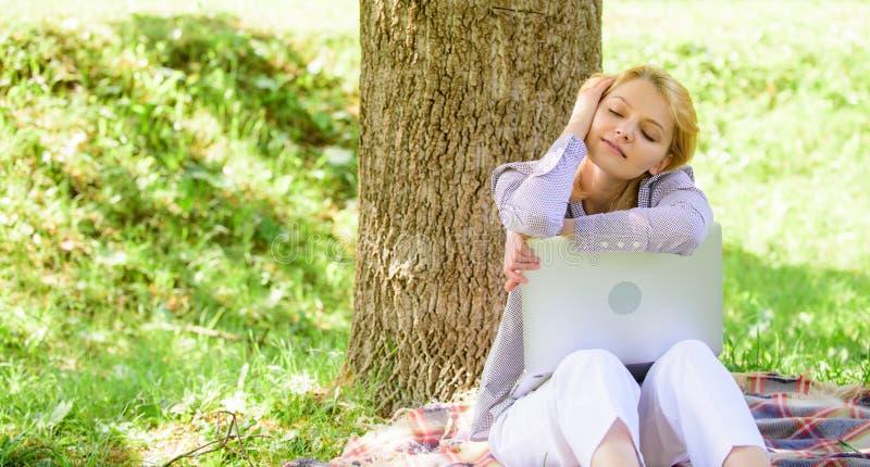 O portátil da menina que sonha no parque senta-se na grama Sonho sobre o projeto bem sucedido Mulher sonhadora com trabalho do po imagem de stock royalty free
