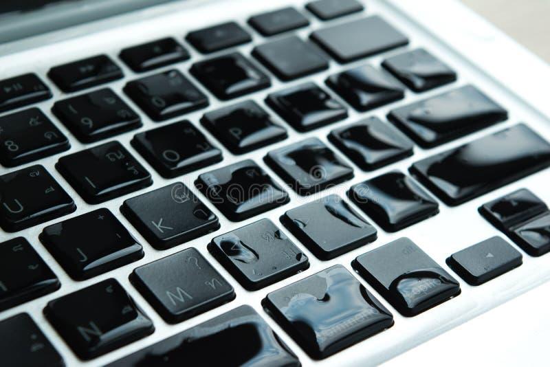 O portátil do computador com dano da gota da água líquido molhou e derramou em k imagens de stock royalty free