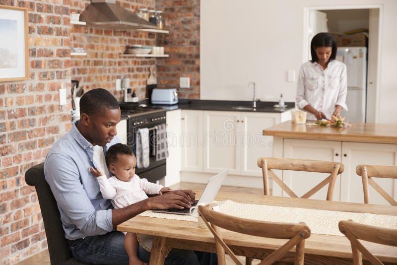 O portátil do uso de And Baby Daughter do pai como a mãe prepara a refeição imagens de stock