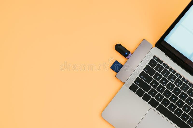 O portátil moderno com tipo-c adaptador e movimentações instantâneas de USB é isolado em um fundo alaranjado foto de stock