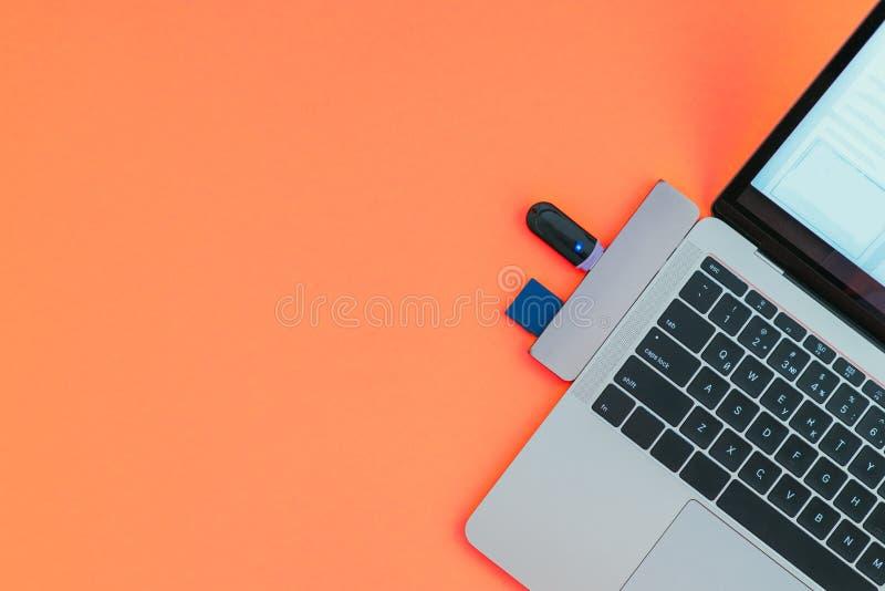 O portátil moderno com tipo-c adaptador e movimentações instantâneas de USB é isolado em um fundo vermelho imagem de stock royalty free