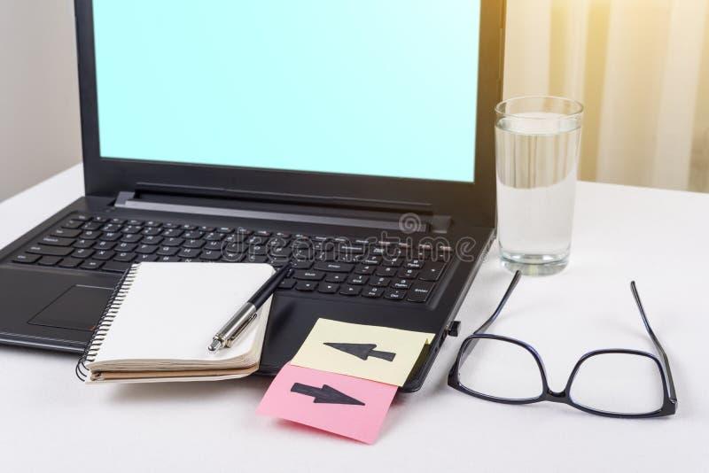 O portátil na mesa do trabalho, ao teclado é etiquetas coladas com setas imagem de stock royalty free