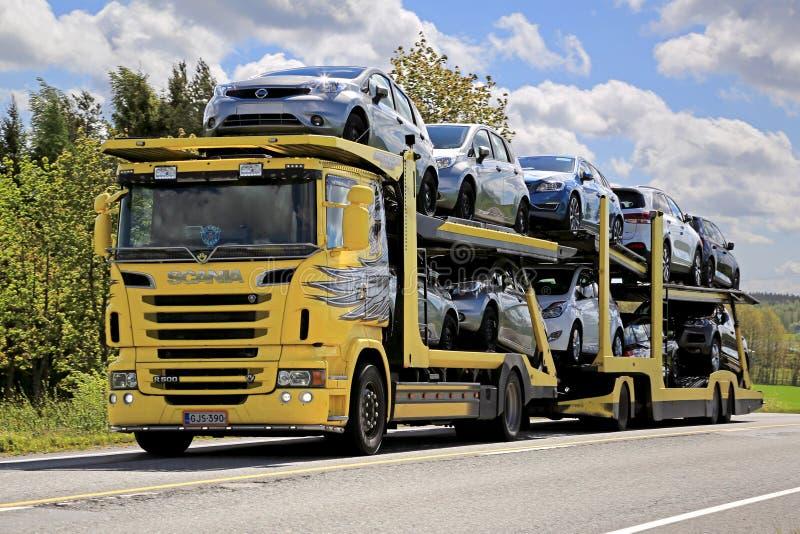 O portador de carro amarelo de Scania R500 transporta carros novos imagens de stock