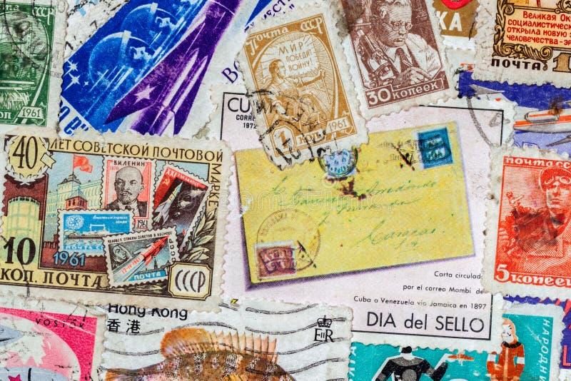 O porte postal usado velho impresso carimba dos vários países, textura do papel como o fundo fotos de stock royalty free