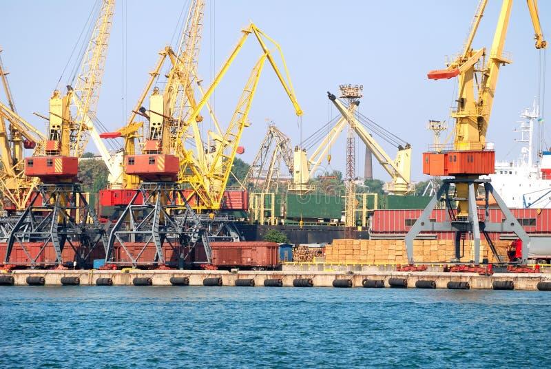 O porto de troca com guindastes, cargas e navio fotografia de stock