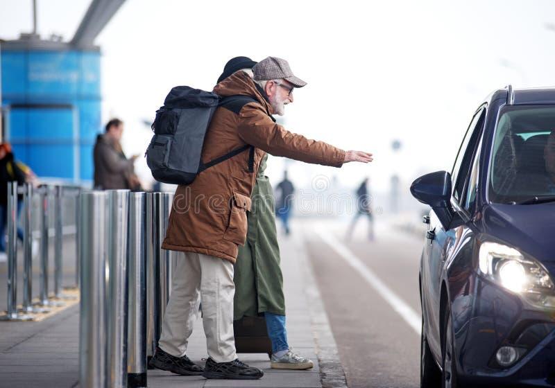 O positivo envelheceu o homem e a fêmea está travando o táxi imagem de stock