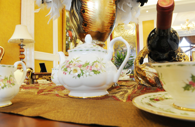 O potenciômetro do chá na tabela de jantar foto de stock