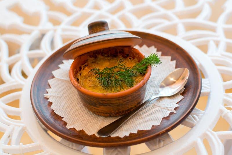 O prato é julienne em um marrom da argila pial com uma tampa fotos de stock royalty free