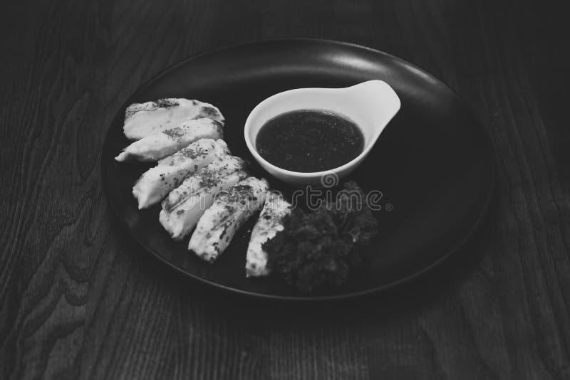 O prato do queijo grelhado serviu com molho da framboesa na placa preta, fundo de madeira Prato de queijo delicioso servido dentr fotografia de stock