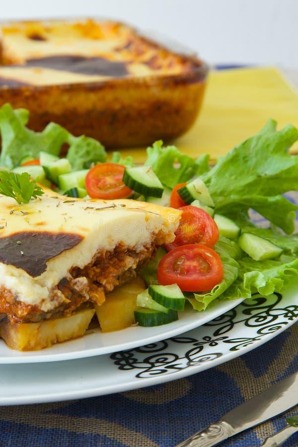 O prato grego tradicional com beringelas, batatas, carne triturada cozeu no molho branco com queijo foto de stock