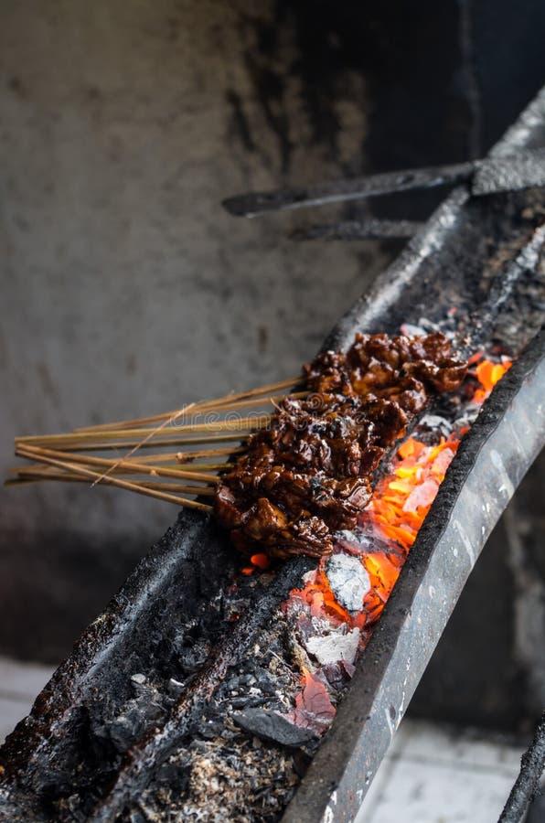 O prato indonésio típico sacia o ayam no mercado de rua local - vertical foto de stock