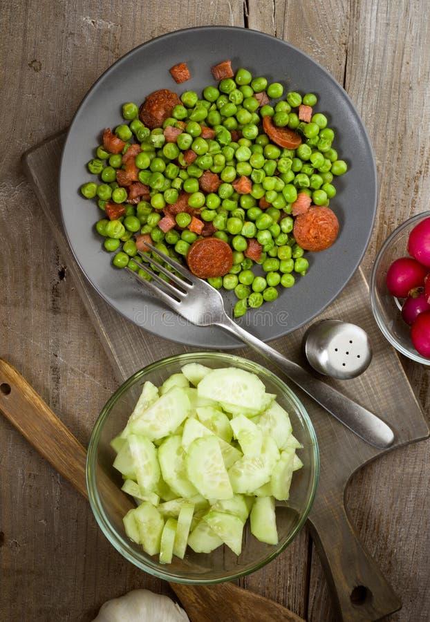 O prato vertical da tomada cozinhou com as ervilhas do presunto e do chouriço no woode velho imagens de stock