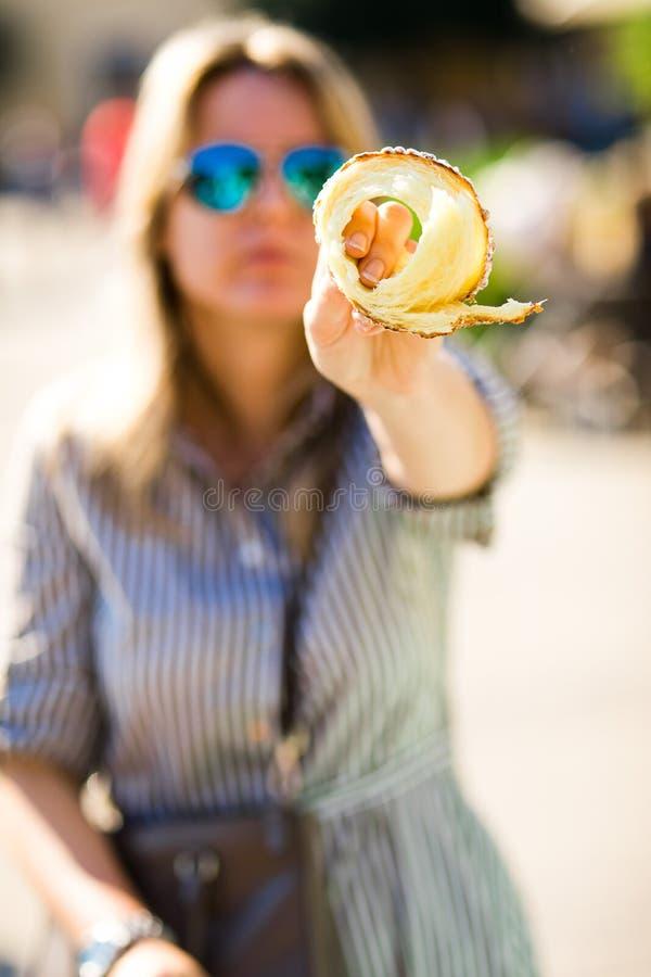 O prazer doce, mulher está mostrando a parte de Trdelnik imagem de stock royalty free
