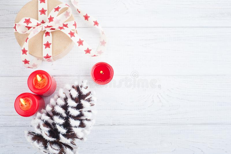 O presente na caixa de kraft com o vermelho stars a fita, iluminado velas e decorat foto de stock royalty free