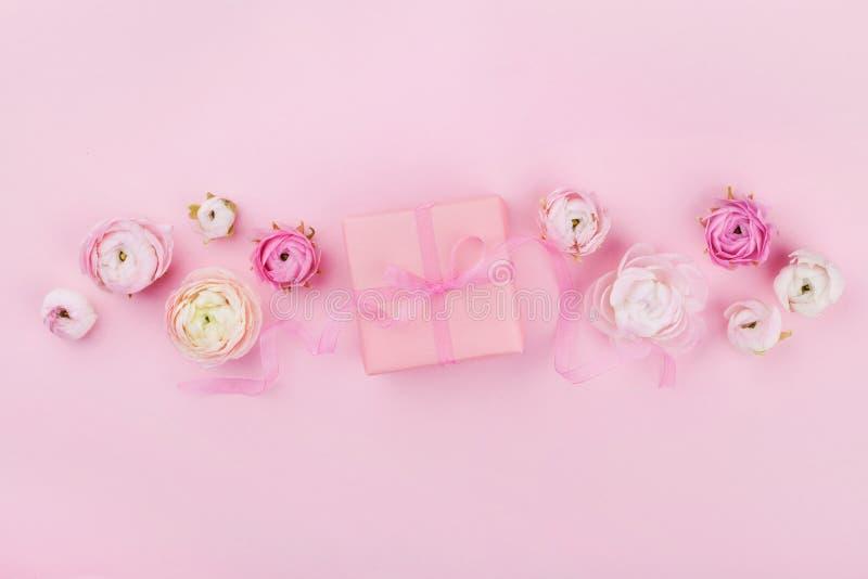 O presente ou a caixa e a mola atuais florescem na mesa cor-de-rosa de cima para do modelo do casamento ou o cartão no dia da mul imagens de stock