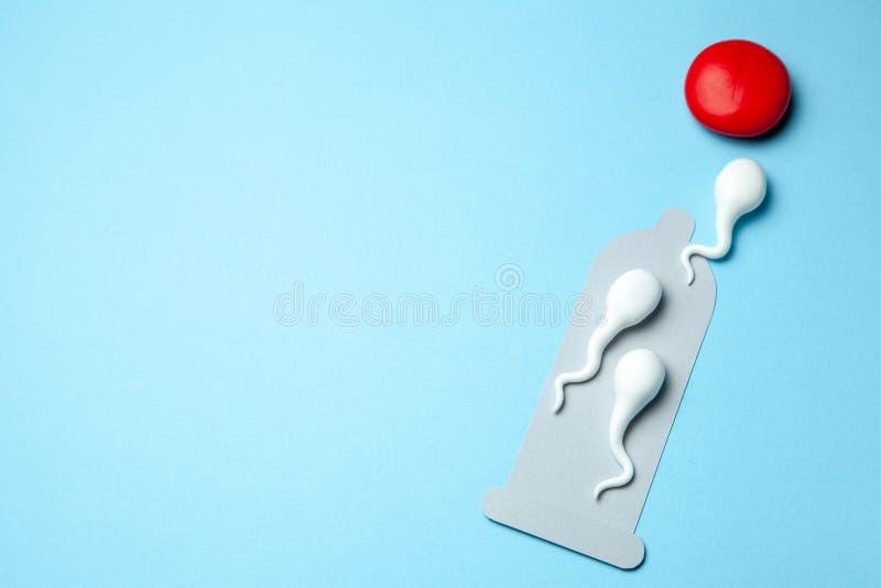 O preservativo danificado rasgado e os preservativos ativos flutuam ao ovo Gravidez inesperada, fecundação do ovo Copie o espaço  foto de stock