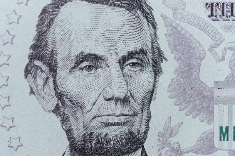 O presidente Abraham Lincoln dos E.U. enfrenta em um macro de cinco notas de dólar, 5 u fotografia de stock