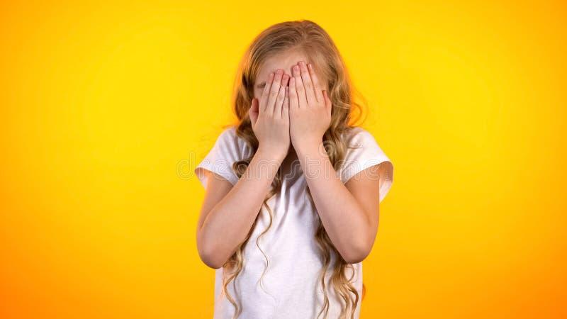 O Preteen amedrontou a cara da coberta da menina com palmas, notícia inesperada dos medos criançolas fotografia de stock
