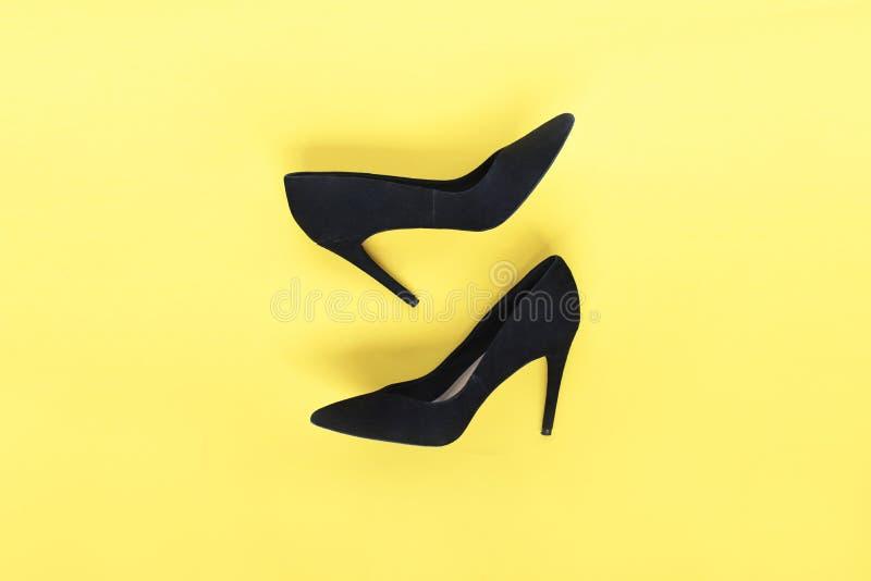 O preto à moda da forma calça os saltos altos no fundo amarelo Configuração lisa, fundo na moda da vista superior Olhar do blogue fotografia de stock royalty free