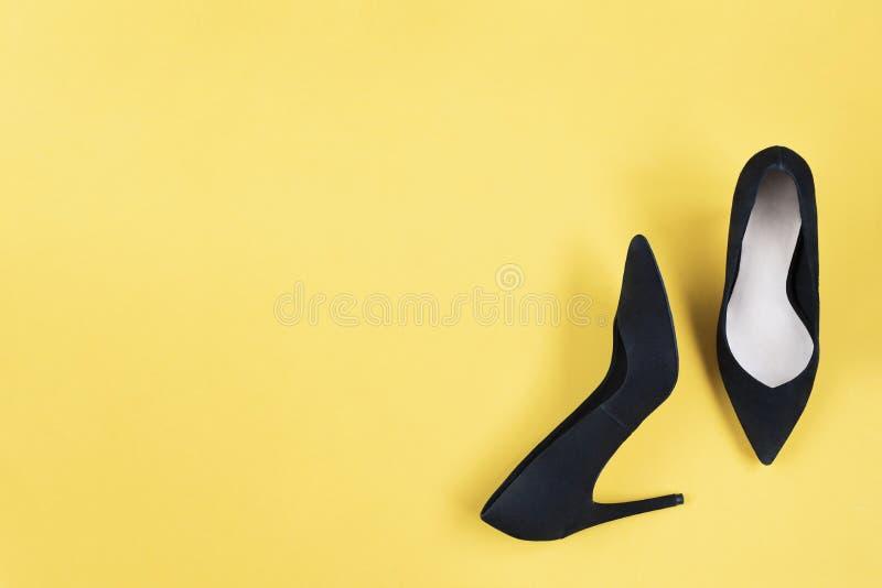 O preto à moda da forma calça os saltos altos no fundo amarelo Configuração lisa, fundo na moda da vista superior Olhar do blogue fotografia de stock