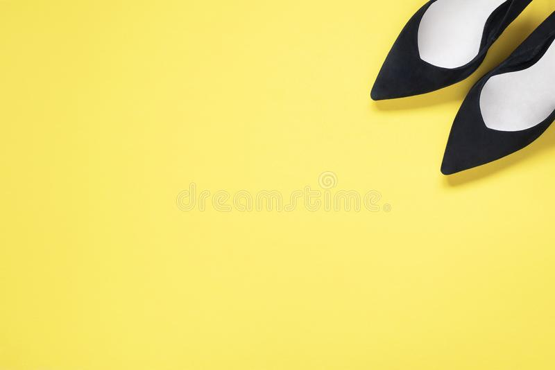 O preto à moda da forma calça os saltos altos no fundo amarelo Configuração lisa, fundo na moda da vista superior Olhar do blogue fotos de stock