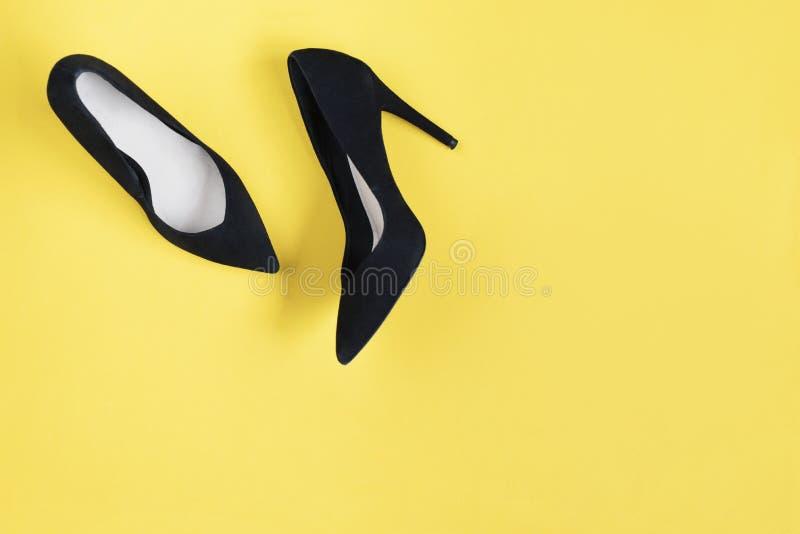 O preto à moda da forma calça os saltos altos no fundo amarelo Configuração lisa, fundo na moda da vista superior Olhar do blogue imagens de stock