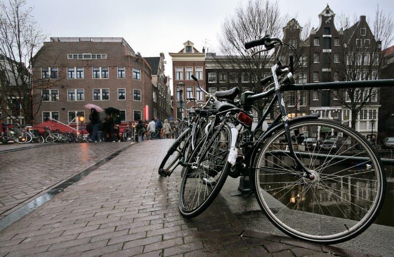 O preto bicycles molhado da chuva estacionada na ponte imagens de stock royalty free