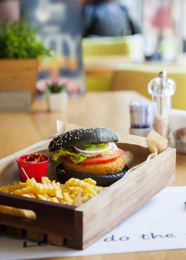 O preto coloriu o hamburguer de dar água na boca, delicioso pequeno na madeira imagens de stock