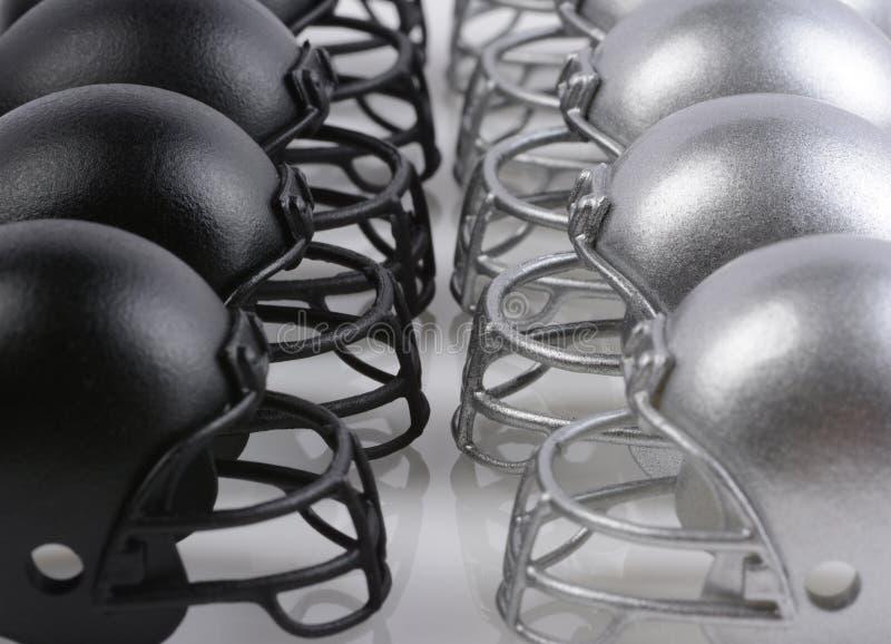 O preto e os capacetes de futebol americano da prata alinharam enfrentando cada um imagens de stock