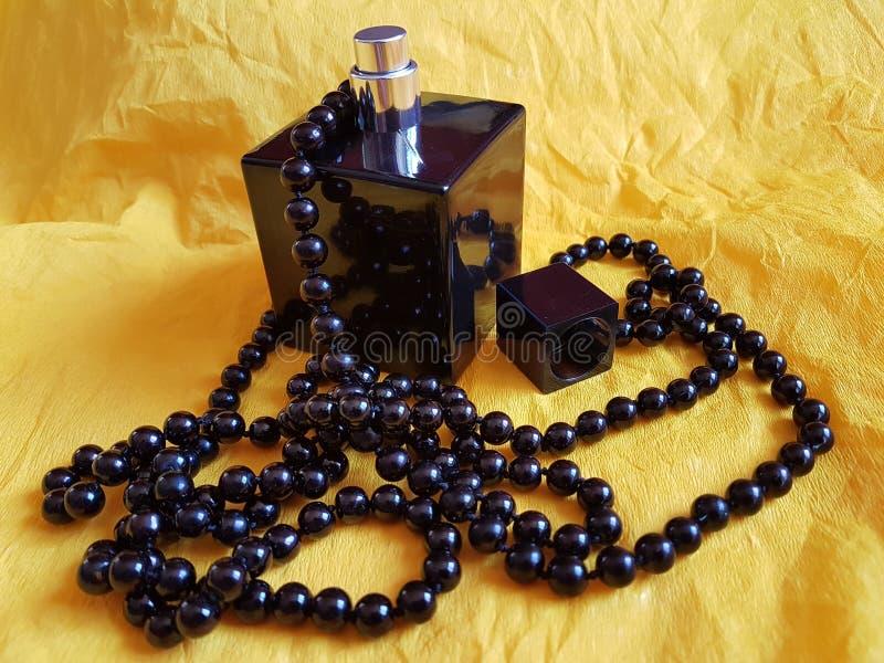 O preto peroliza o necklale com a garrafa de perfume no fundo amarelo fotografia de stock