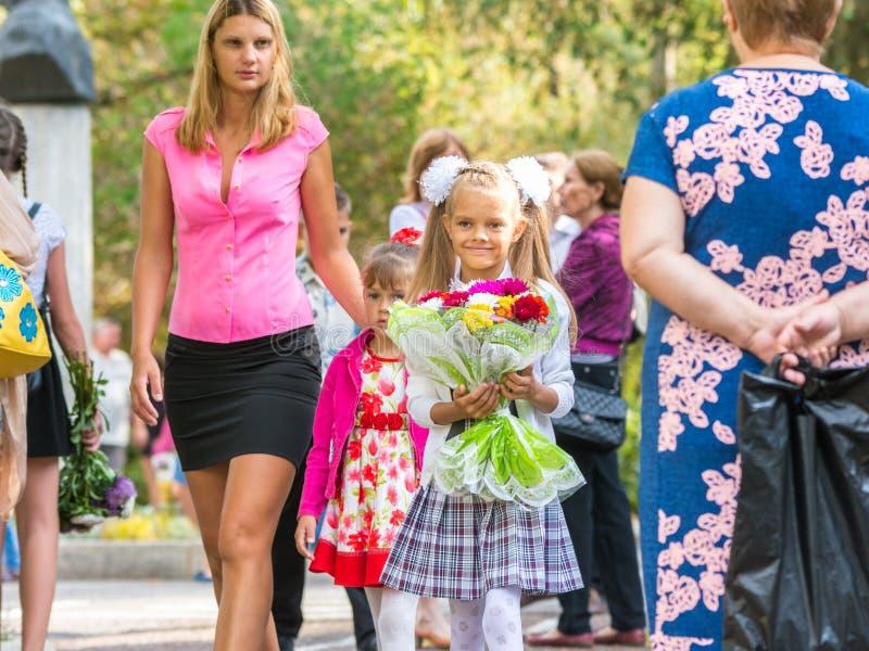 O primeiro graduador vai escola com suas mãe e irmã mais nova imagem de stock royalty free