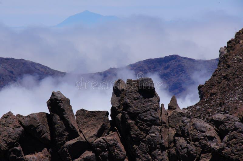 O primeiro plano de rochas da lava, da montanha vulcânica e da cimeira do Teide fotos de stock royalty free