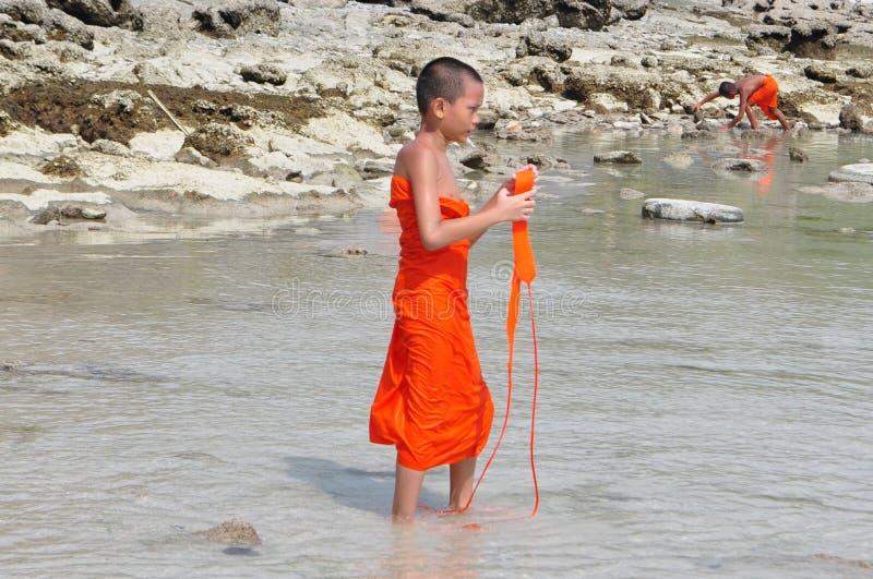 O principiante budista tailandês novo aprecia a praia em Tailândia imagens de stock