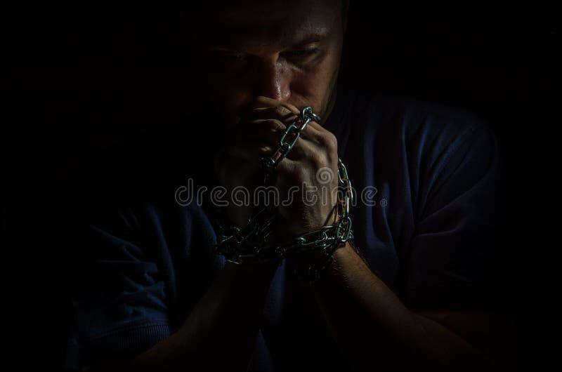 O prisioneiro arrependido do homem com suas mãos shackled nas correntes em um fundo escuro fotos de stock royalty free