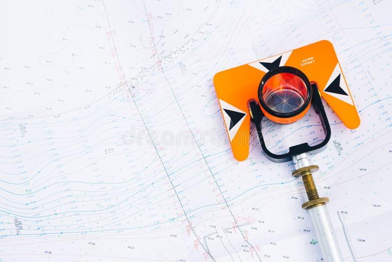 O prisma alaranjado do teodolito encontra-se em mapas geodésicos de um fundo da área foto de stock royalty free