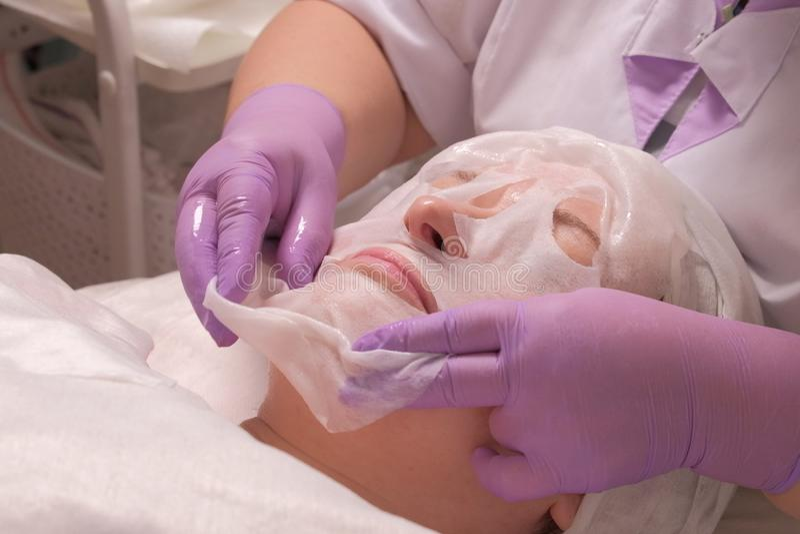 O procedimento do rejuvenescimento da pele no escritório médico Um cosmetologist profissional em luvas lilás põe uma máscara sobr imagem de stock