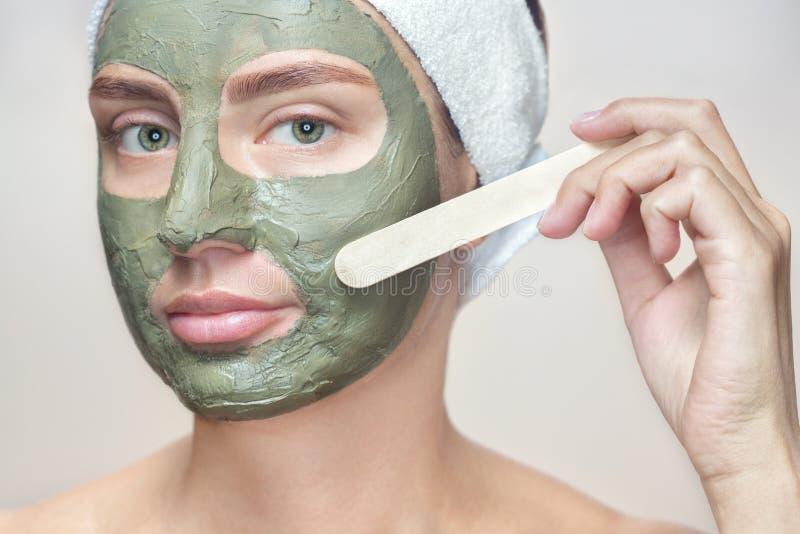 O procedimento para aplicar uma máscara da argila à cara de uma mulher bonita fotografia de stock
