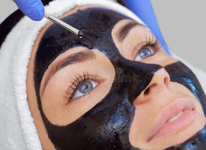 O procedimento para aplicar uma máscara preta à cara de uma mulher bonita imagens de stock