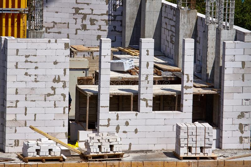 O processo de construir o assoalho seguinte de um prédio, de apoios do cimento e de paredes do bloco de cinza, foco seletivo imagem de stock royalty free