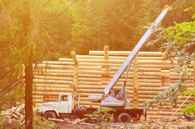 O processo de construir uma casa de madeira dos feixes de madeira da forma cilíndrica Guindaste na condição de trabalho fotografia de stock