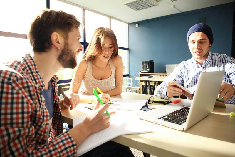 O processo de Coworking, desenhistas team o escritório moderno de trabalho Gerente criativo novo da foto que mostra o monitor sta foto de stock