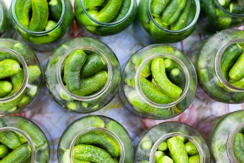 O processo de enlatar pepino conservados para o inverno, conserva pepinos nos frascos de vidro fotos de stock