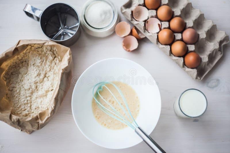 O processo de fazer a massa, a mão da mulher chicoteia ovos e farinha na composição colocada lisa da bacia dos ingredientes e da  imagem de stock