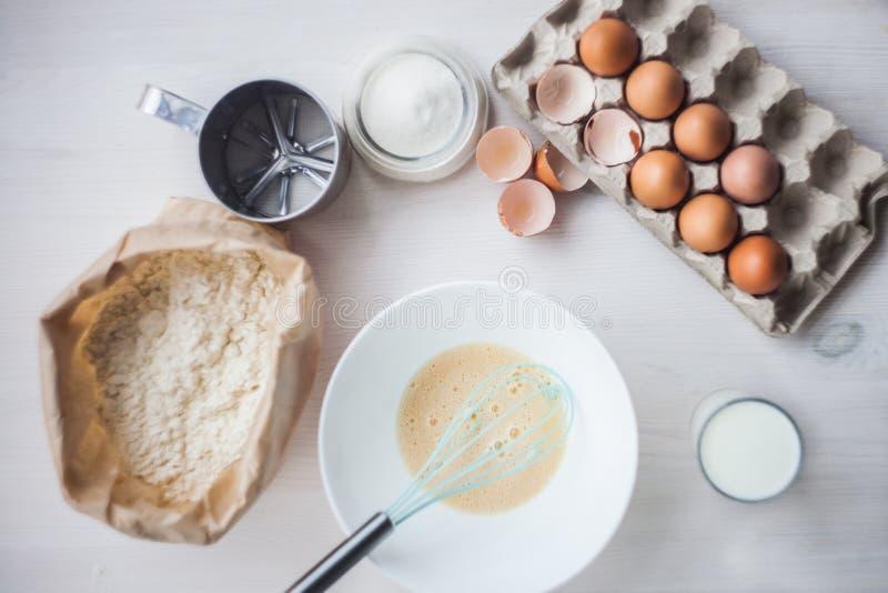 O processo de fazer a massa, a mão da mulher chicoteia ovos e farinha na composição colocada lisa da bacia dos ingredientes e da  foto de stock royalty free