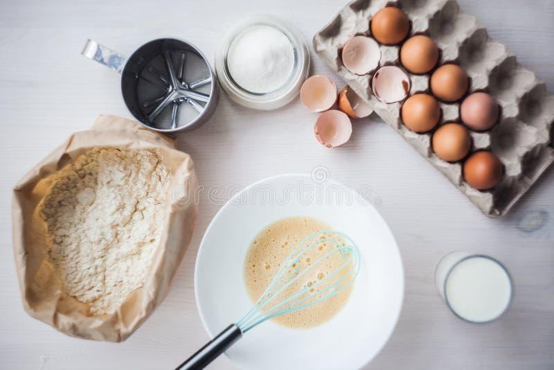 O processo de fazer a massa, a mão da mulher chicoteia ovos e farinha na composição colocada lisa da bacia dos ingredientes e da  imagens de stock royalty free