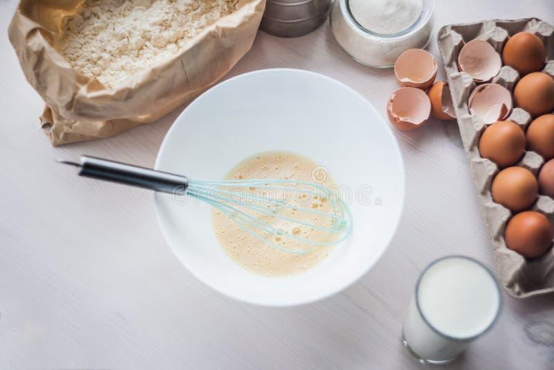 O processo de fazer a massa, a mão da mulher chicoteia ovos e farinha na composição colocada lisa da bacia dos ingredientes e da  imagem de stock royalty free