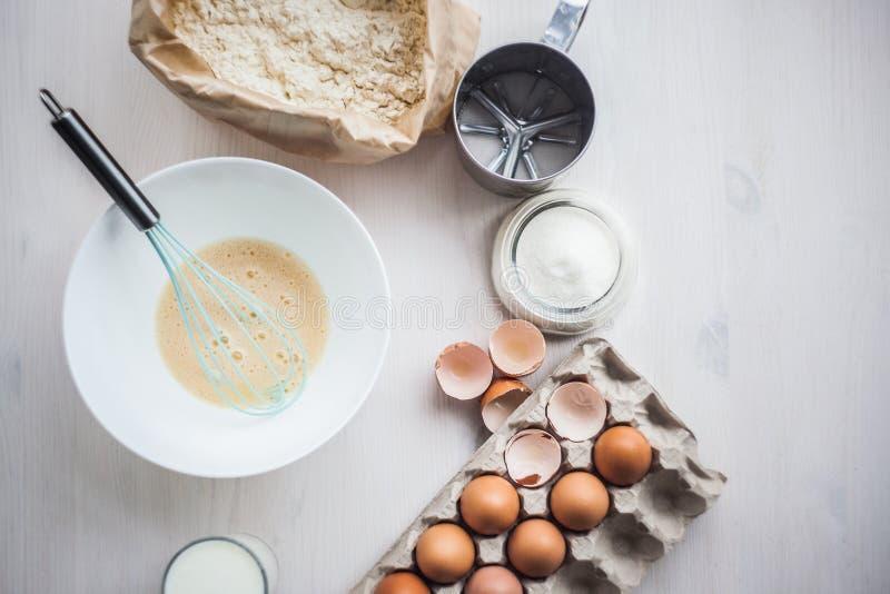 O processo de fazer a massa, a mão da mulher chicoteia ovos e farinha na composição colocada lisa da bacia dos ingredientes e da  fotografia de stock royalty free