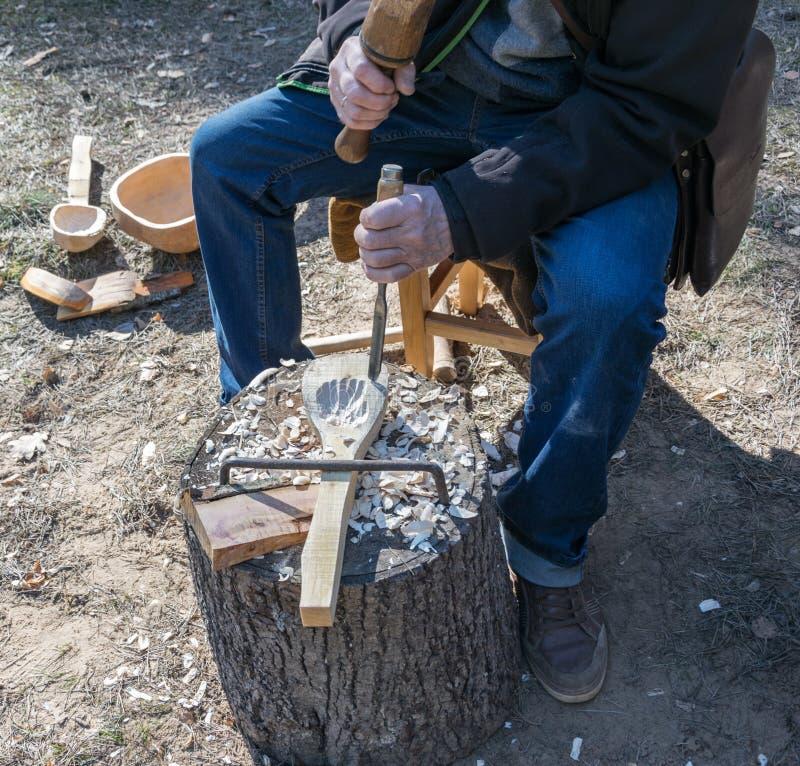 O processo de fazer uma colher de madeira imagens de stock